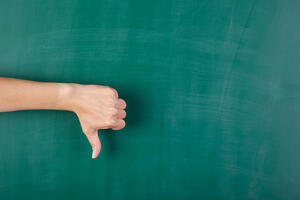 Closeup of woman's hand gesturing thumbs down against chalkboard