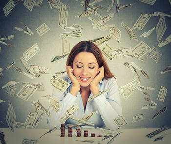 Excited happy young woman sitting at table with growing stack of coins under a money rain isolated on gray wall background. Positive emotions financial success luck good economy concept-1