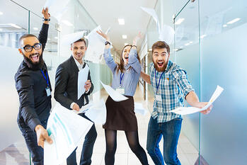Group of joyful excited business people throwing papers and having fun in office-4