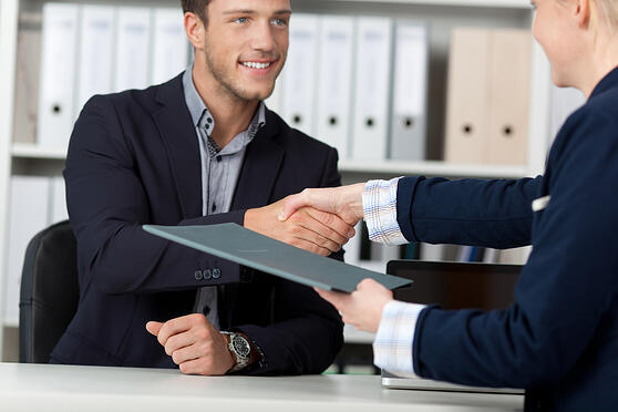 Happy businessman shaking hands with a female interviewer in office-2