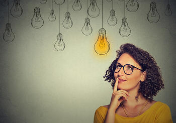 Thinking woman in glasses looking up with light idea bulb above head isolated on gray wall background-2