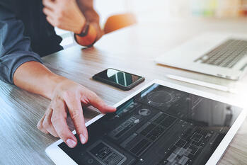 Website designer working digital tablet and computer laptop with smart phone and graphics design diagram on wooden desk as concept-1