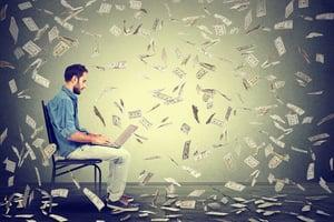 Young man using a laptop building online business making dollar bills cash falling down. Beginner IT entrepreneur under money rain. Success economy concept-1