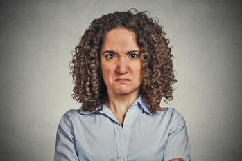 headshot angry woman isolated on grey wall background. Negative face expression body language