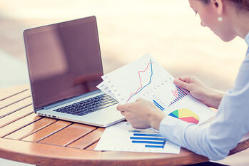 woman investment consultant analyzing company annual financial report balance sheet statement working with documents graphs. Stock market, office, tax, education concept. Hands with charts papers